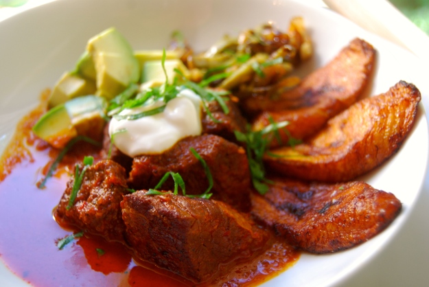 This braised beef dish gets its vibrant red color from dried pasilla, arbol, and guajillo chilies