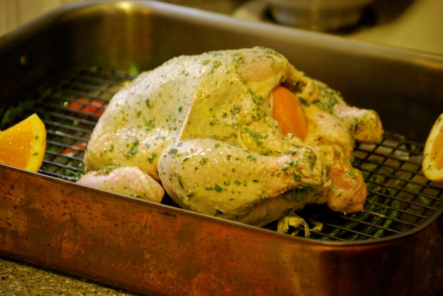 Herb butter smeared all over the chicken - stuffed with garlic and oranges