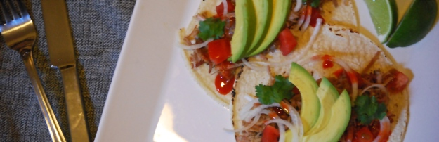 Carnitas - braised pork tacos with white onion, tomato, cilantro, avocado, lime, hot sauce